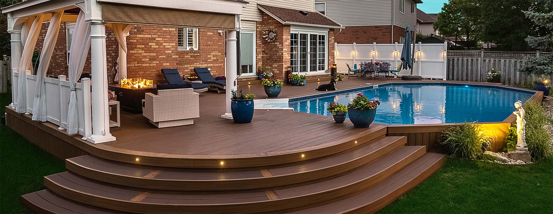 Deck with curved steps and a pool